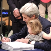 John Kerry and his Granddaughter signing the treaty for the US