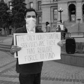 Man Wearing a Mask Displays His Sign
