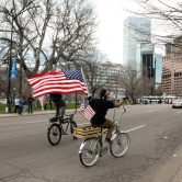 Two Men on a Bike Wave the Flag in Protest